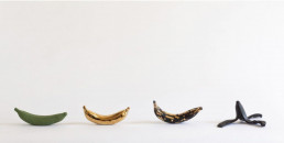 """Acquired by the Art Museum of Texas SL, Anita Becerra """"Overripe"""" Porcelain, glaze and 14K gold luster Installation 2/2 $1500 Individual 14K banana (4/4) $500"""